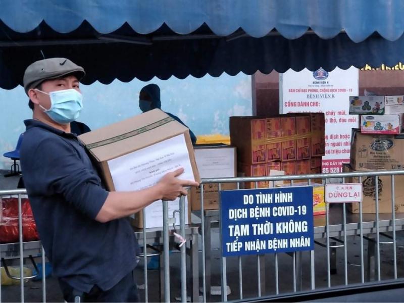 Phó giáo sư, tiến sĩ, bác sĩ Hoàng Bùi Hải đang bê những thùng dầu gội Hương Xưa cho bệnh nhân Bệnh viện K.
