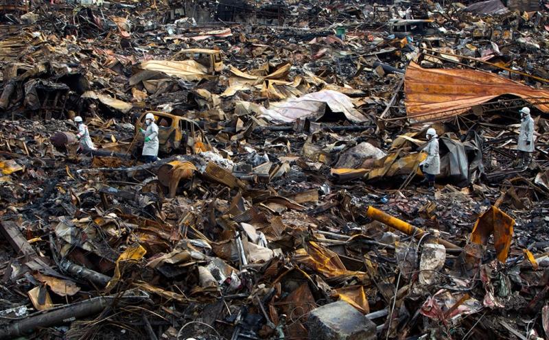 Các công nhân tìm kiếm tìm trong đống đổ nát ở tỉnh Miyagi. Ảnh: Reuters.