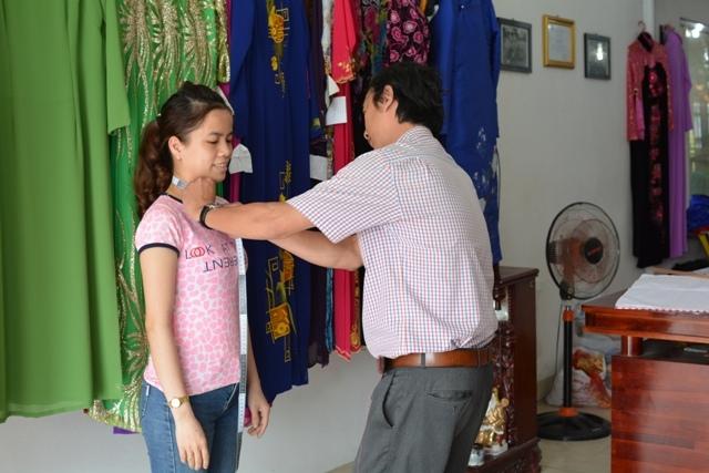 Anh Nguyễn Quốc Hòa - chủ nhà may Minh Tâm đang may đo áo dài cho khách hàng