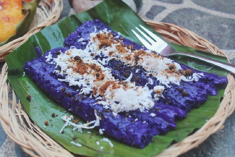 Puto Bumbong được phết bơ lên trên kèm theo một lớp dừa tươi nạo và đường muscovado.
