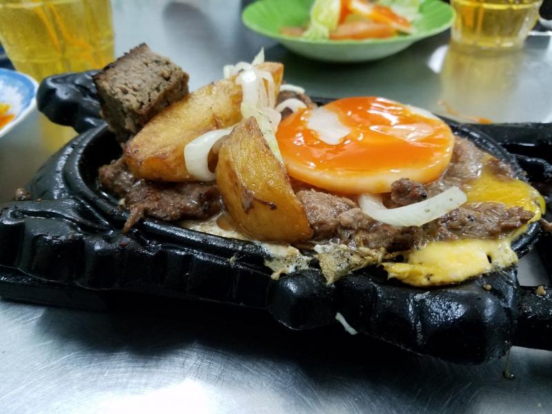 Một phần đầy đủ của quán  gồm thịt bò, khoai tây chiên, trứng ốp-la, pa-tê, có kèm dĩa xà lách, dưa leo, cà chua