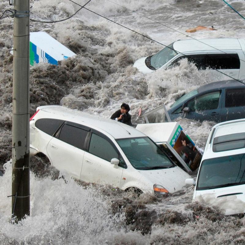 Một phóng viên bị sóng thần cuốn trôi khi đang tác nghiệp. Ông đã thoát chết nhờ bám vào một sợi dây và trèo lên một đống than. Ảnh: Reuters.