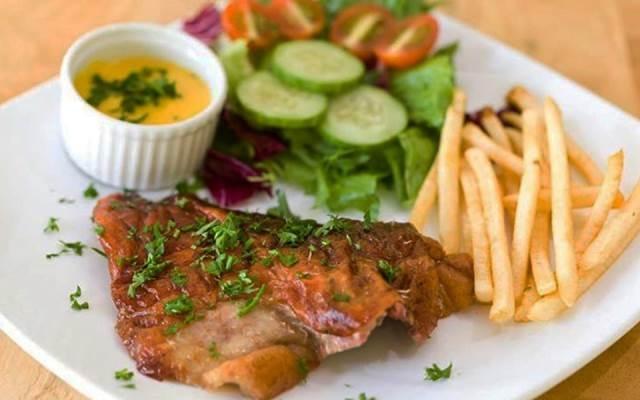 Một đĩa bò beefsteak gồm khoai tây, nước chấm và rau củ quả