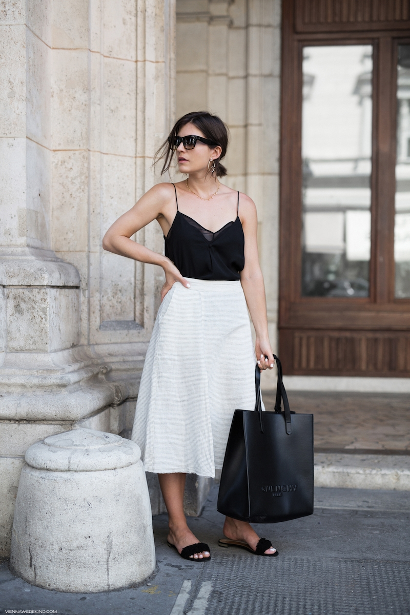 Chân váy chữ A dáng dài bản xòe rộng màu trắng làm nổi bật set đồ trên nền tông đen