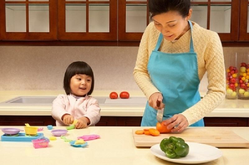 Bé bắt chước mẹ làm bếp.