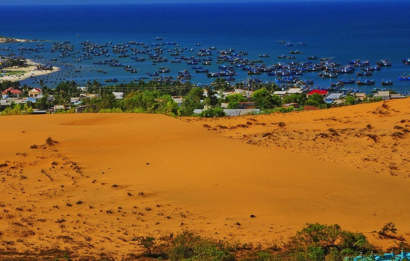 The red sand dunes are as beautiful and poetic as standing in the middle of the desert right next to the beach