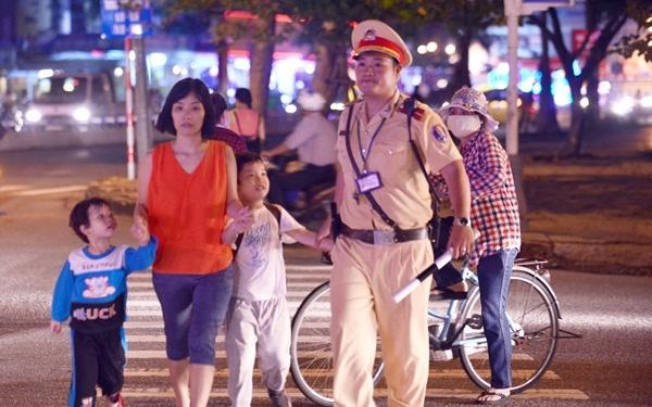 Công an giao thông dẫn người dân qua đường lúc đang làm nhiệm vụ