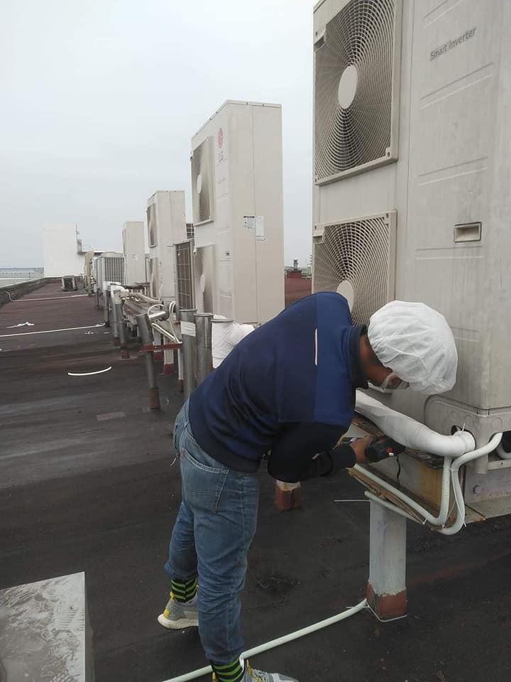 Hai nhân viên đang sửa chữa điều hòa