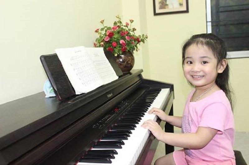 Bé học chơi đàn piano.