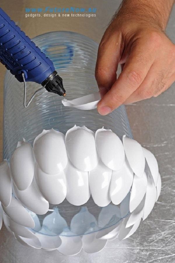 Phết keo và dán những chiếc thìa nhựa bỏ cán quanh chai nhựa