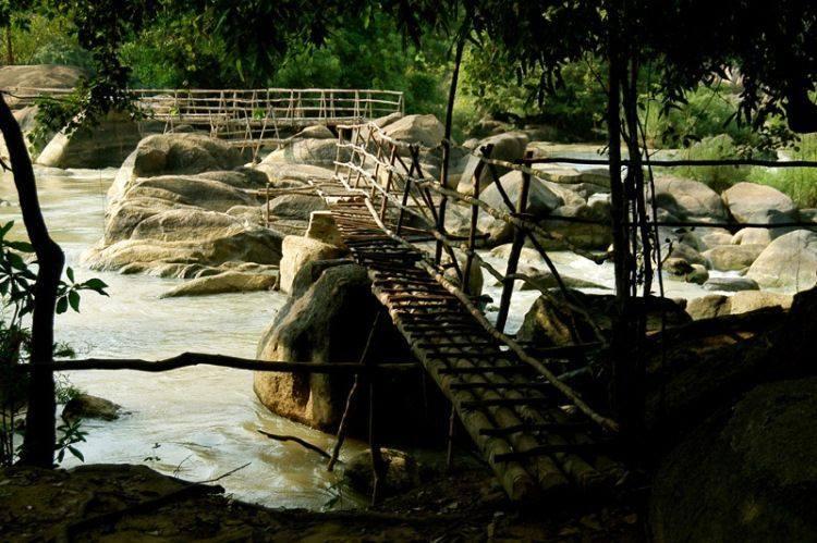 Chiếc cầu mộc mạc đơn sơ bắt ngang qua con suối nhỏ.
