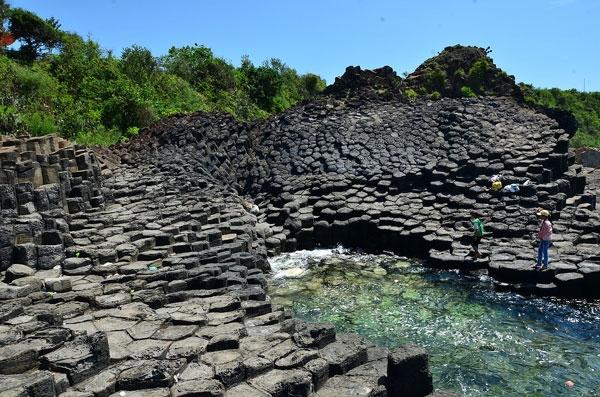 Những khối đá đĩa đen tuyền phủ ánh sáng rực rỡ như sáp ong