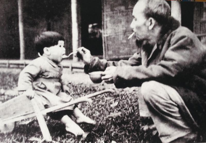 Bác Hồ bón cơm cho cháu bé khi đến thăm một trại nhi đồng ở Việt Bắc, năm 1950