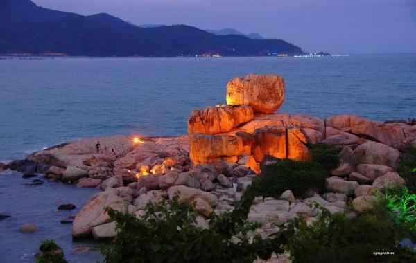 Khi màn đêm buông xuống, những ánh đèn phủ lên phiến đá khổng lồ, khiến bỗng chốc chúng biến thành những viên than hồng lấp lánh.