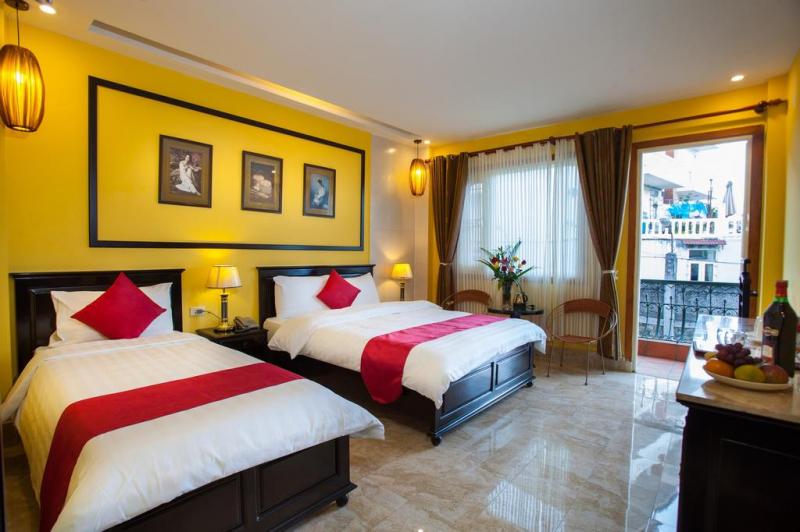 Không gian phòng ngủ khách sạn với tong màu vàng chủ đạo được thiết kế giản dị, nhưng vẫn rất đẹp mắt.