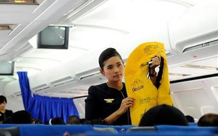 Tiếp viên hàng không đang hướng dẫn an toàn bay cho hành khách.