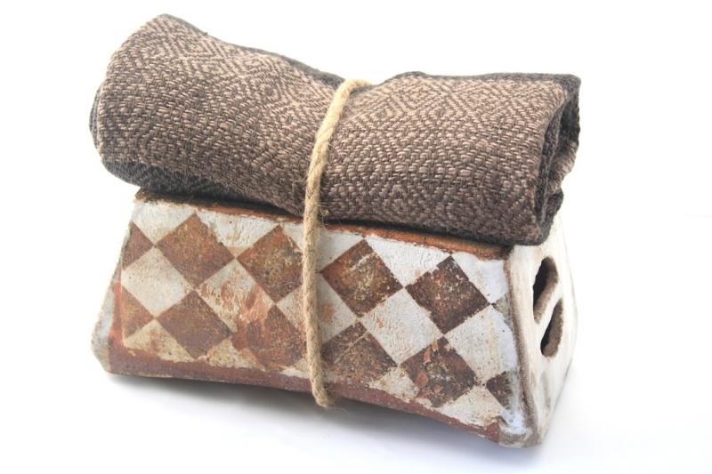 Chiếc gối bao gồm một bàn tọa gỗ và một tấm thảm cuộn tròn