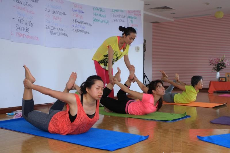 Giáo viên chỉnh từng động tác cho người tập Yoga