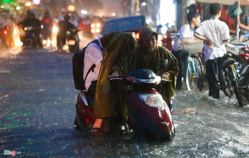 Bức ảnh của tác giả Ngô Trần Hải An ghi lại cảnh người mẹ dắt con ngồi trên xe, qua nơi nước ngập.