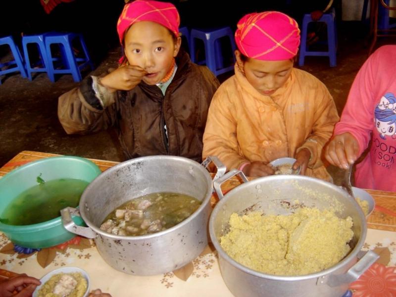 Hai chị em người Mông đang ăn mèn mén