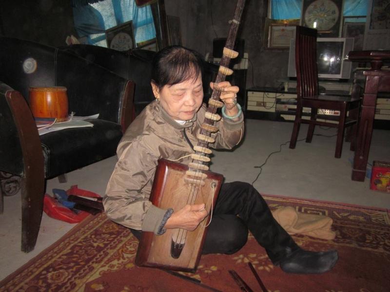 Nghệ nhân Nguyễn Thị Tam bên chiếc đàn đáy cổ