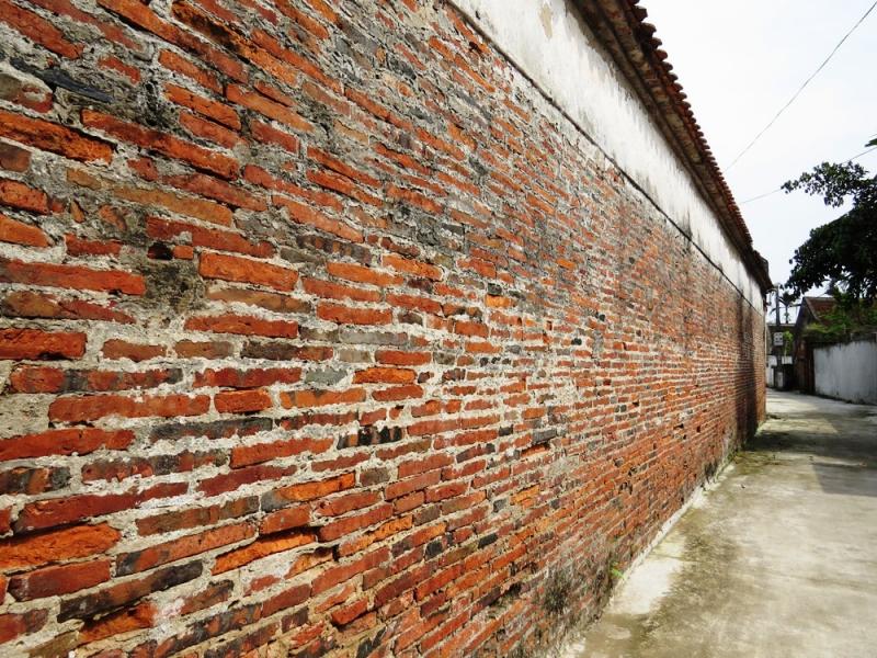 Tường nhà được xây bằng gạch đất nung bản mỏng, kích thước mỗi viên gạch dài tới 40 cm, rộng 30 cm