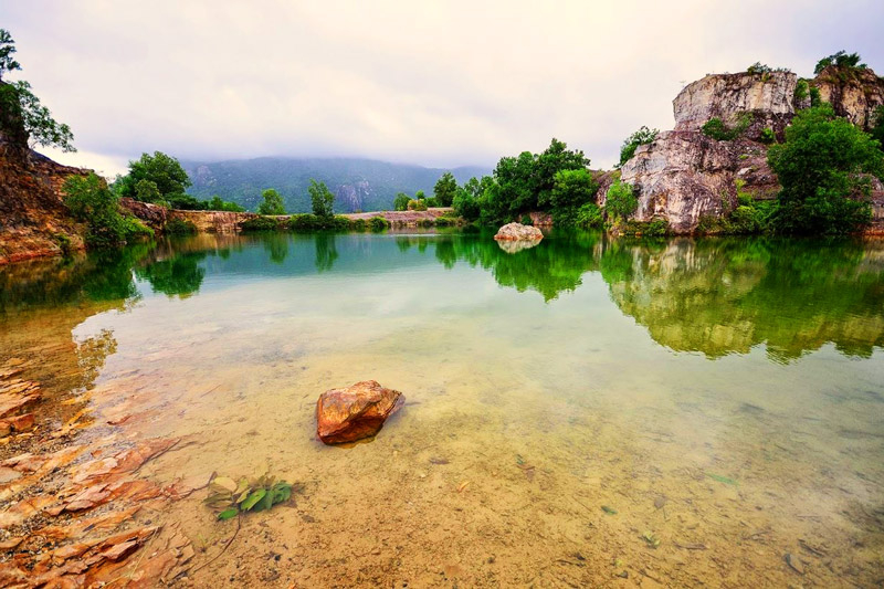 The cliffs and stone pillars of Ta Pa mountain are reflected in the blue lake bottom