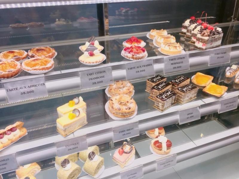 Quầy trưng bày với đủ loại bánh và giá cả đính kèm