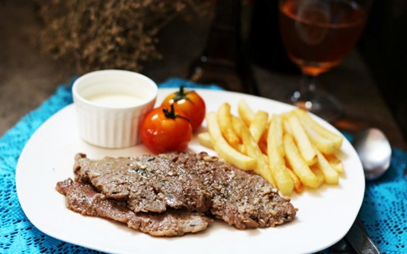Bò bít tết cùng khoai tây chiên và rượu vang trắng