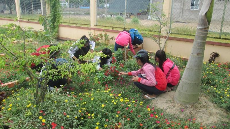 Các em đội viên chăm sóc bồn hoa cây cảnh chào mừng 26 - 3