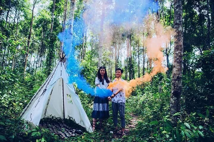 Hai bạn trẻ đang chụp ảnh đôi  phong cách cắm trại với pháo màu