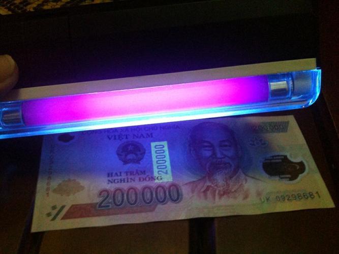 Soi tờ tiền dưới nguồn sáng để phân biệt