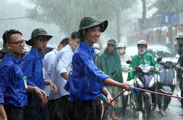 Không ngại mưa gió giúp đỡ người xung quanh qua vùng nước ngập.