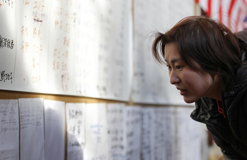 Một người đang tìm danh sách những người sống sót ở một trung tâm sơ tán ở tỉnh Iwate. Ảnh: Reuters.