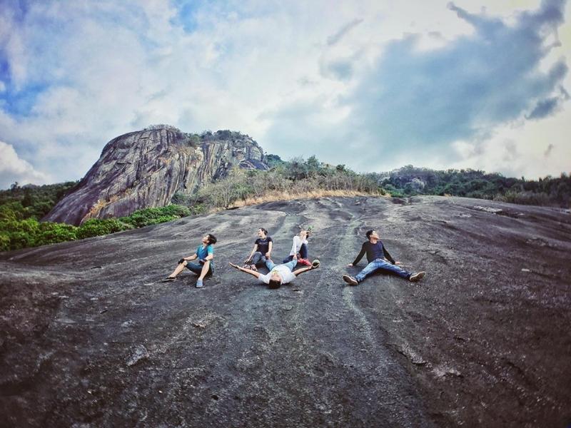 Các bạn trẻ thích thú tạo dáng trên tảng đá, phía sau là tảng đá Đầu Voi