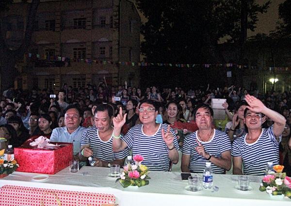 Thầy Bình( ngồi giữa) cùng các thầy cô trong trường mặc áo kẻ trong lễ tốt nghiệp của học sinh