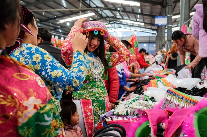 Một cô gái đang thử khăn đội đầu, loại trang sức truyền thống của người dân tộc Mông thường được sử dụng trong các dịp lễ hội.