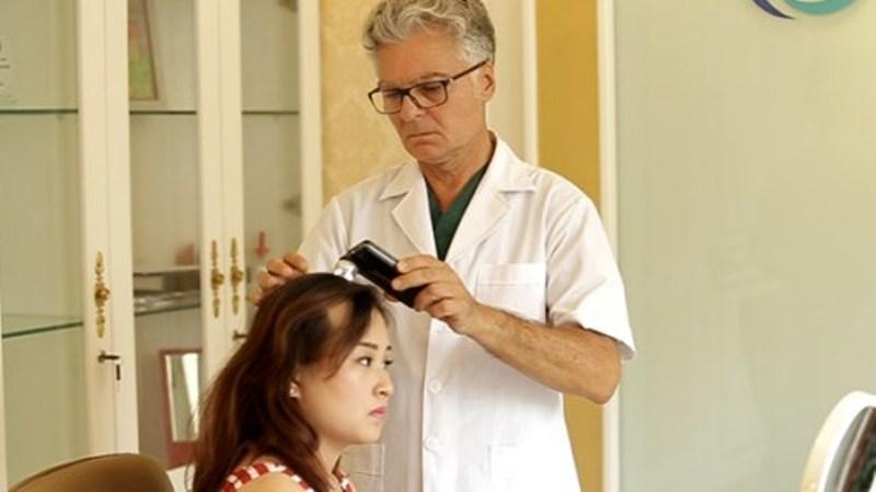 Bác sĩ khám xác định tình trạng rụng tóc ở bệnh nhân